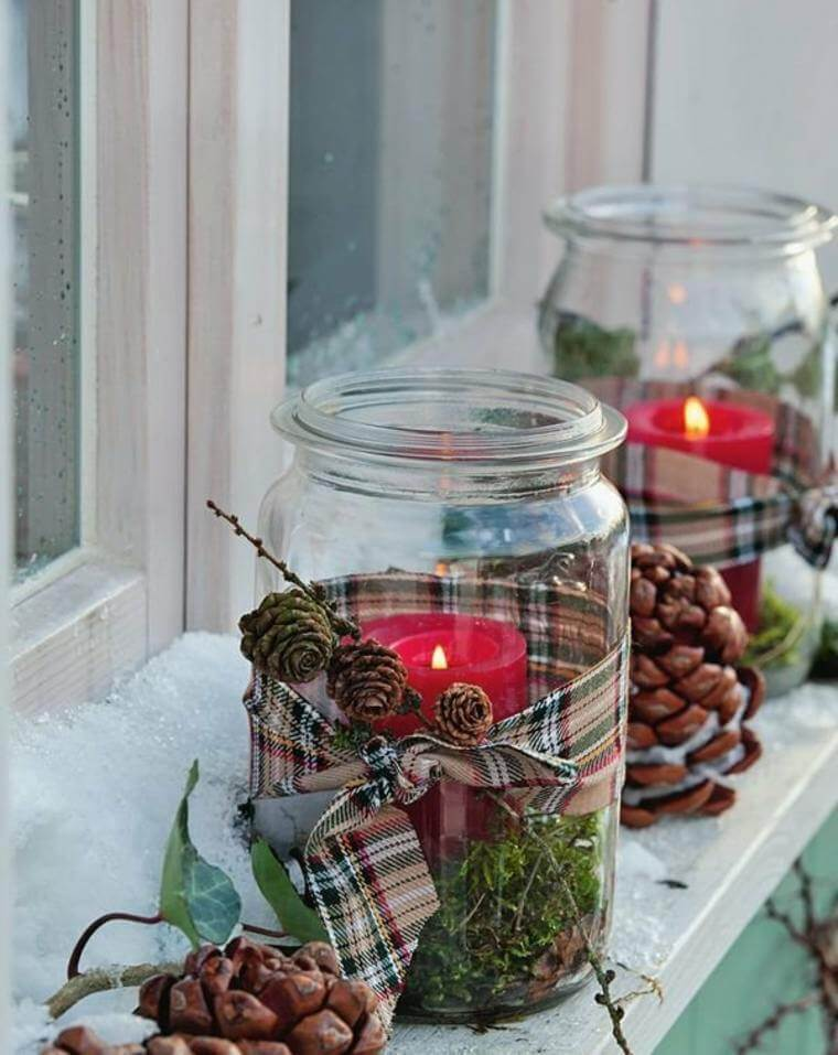 Decorative composition with candle holders, pine cones and a ribbon