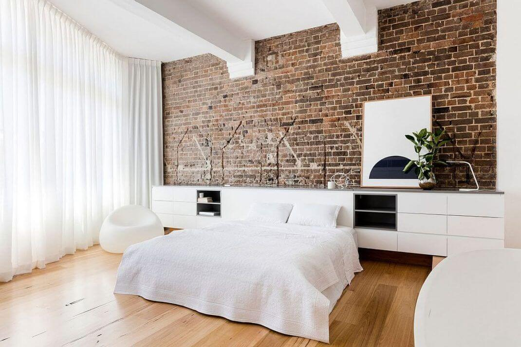 White bedroom with brick wall (1)